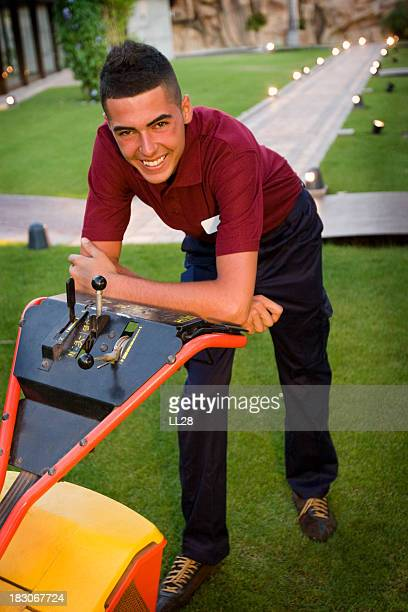 Gardener smiling a leaning on lawnmower