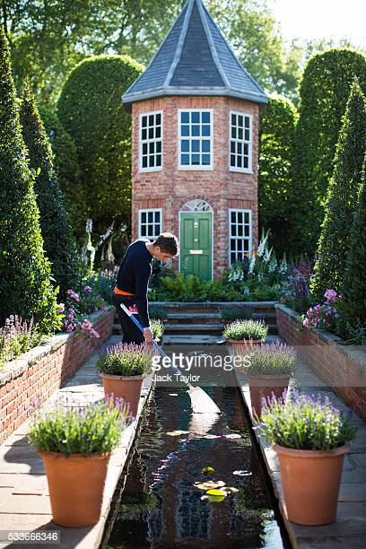 A gardener tends to a pond in 'The Harrods British Eccentrics Garden' at the Chelsea Flower Show on May 23 2016 in London England The prestigious...