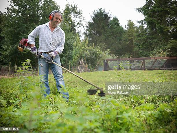 Gardener wearing ear protectors and visor using strimmer