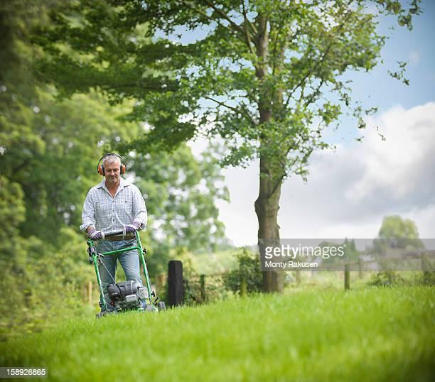 Gardener wearing ear protectors mowing lawn with lawn mower
