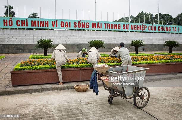 Gardeners cultivate a flowerbed in front of the Ho Chi Minh mausoleum in Hanoi on October 31 2016 in Hanoi Vietnam