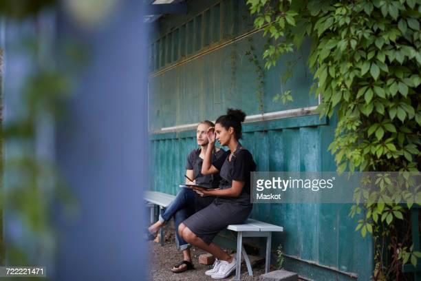 Gardeners looking away while sitting on bench at yard