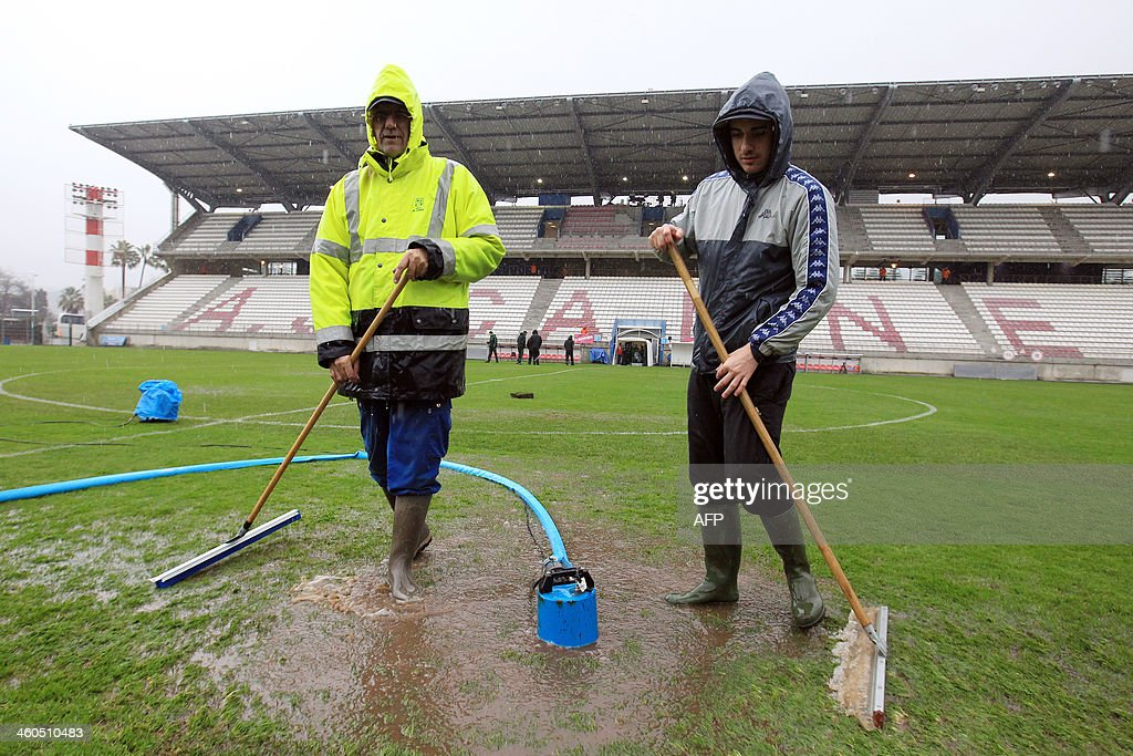 Gardeners try to remove water from the pitch of the Coubertin stadium in Cannes, southeastern France, on January 4, 2014 before a French Cup football match between Cannes and Saint-Etienne. The match has been postponed until tomorrow because of the weather condition. AFP PHOTO / JEAN CHRISTOPHE MAGNENET