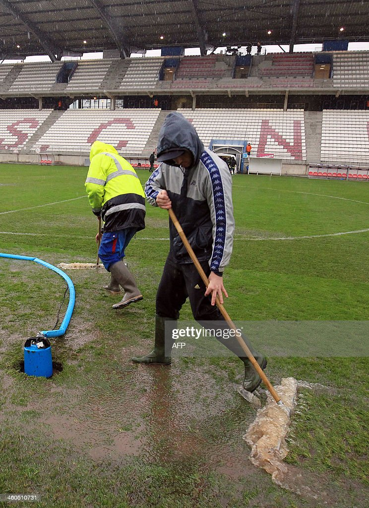 Gardeners try to remove water from the pitch of the Coubertin stadium in Cannes, southeastern France, on January 4, 2014 before a French Cup football match between Cannes and Saint-Etienne. The match has been postponed until tomorrow because of the weather condition.