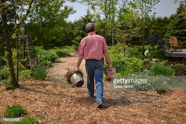 Gardening expert Mark Cullen walks with two container plantings in the backyard of his home