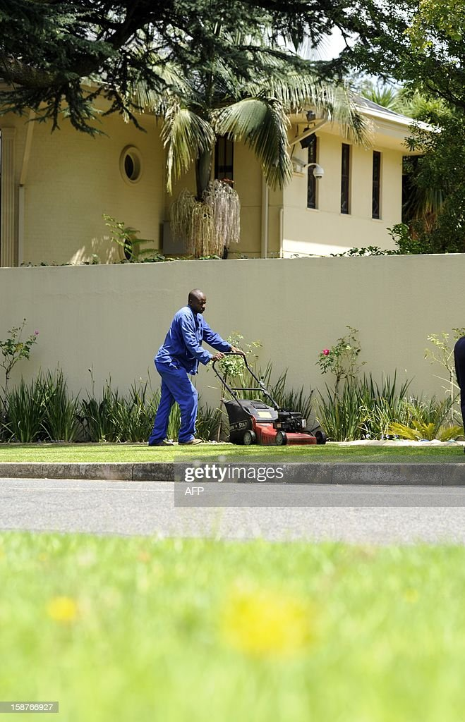 Gardners mow the grass outside the residence of Nelson Mandela in Johannesburg on December 28, 2012. South Africa's anti-apartheid icon Nelson Mandela was recovering at his Johannesburg home today, convalescing and receiving further care after a nearly three-week hospital stay, officials said.