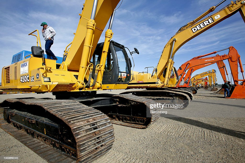 Gared Rank looks at hydraulic excavators made by Hitachi Ltd., Liebherr, Caterpillar Inc., and Deere & Co. before a Ritchie Bros. Auctioneers Inc. industrial equipment auction in Dunnigan, California, U.S., on Thursday, May 20, 2010. More than 1,400 lots were offered during the multi-million dollar unreserved public auction through Ritchie Bros., the world's biggest auctioneer of industrial equipment. Photographer: Ken James/Bloomberg via Getty Images