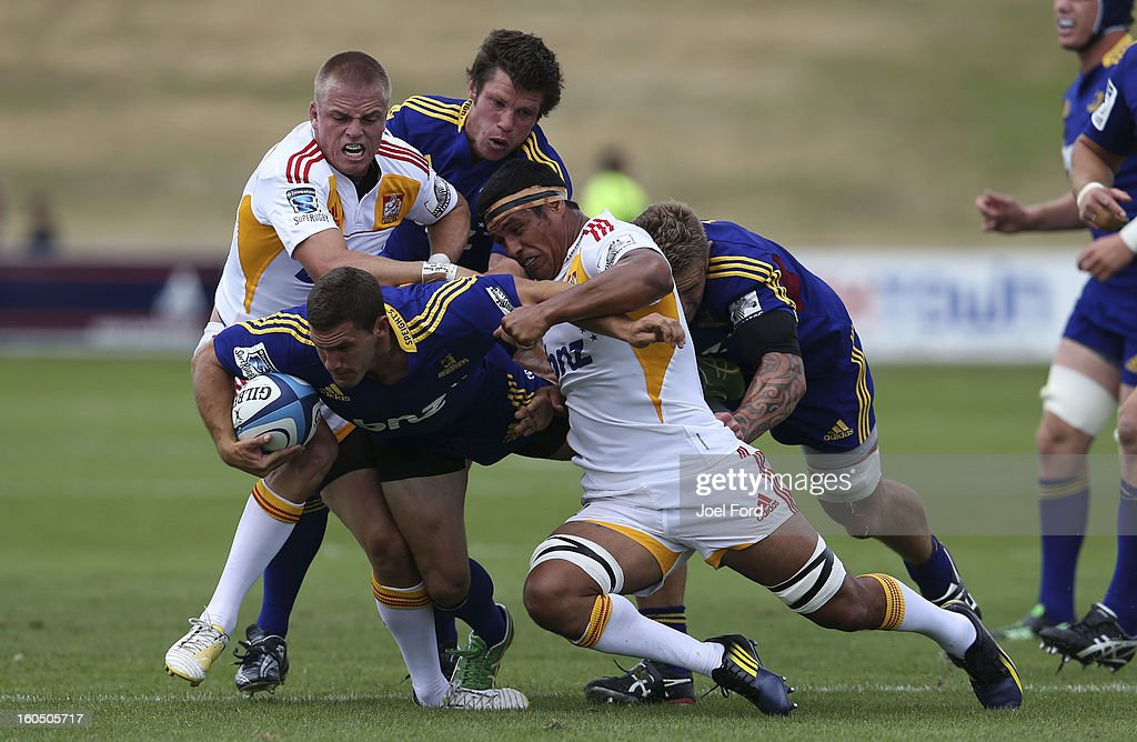 Gareth Anscombe and Tanerau Latimer of the Chiefs tackle Shaun Treeby of the Highlanders during the 2013 Super Rugby pre-season friendly match between the Chiefs and the Highlanders at Owen Delany Park, Taupo on February 2, 2013 in Taupo, New Zealand.