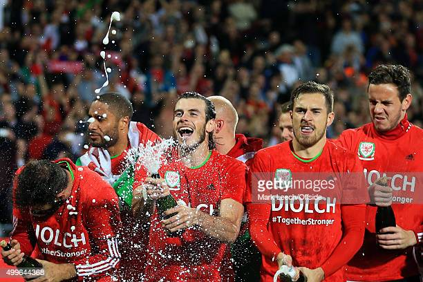 Gareth Bale and Aaron Ramsey of Wales celebrate among his team mates spraying Champagne during the UEFA EURO 2016 Group B Qualifier between Wales and...