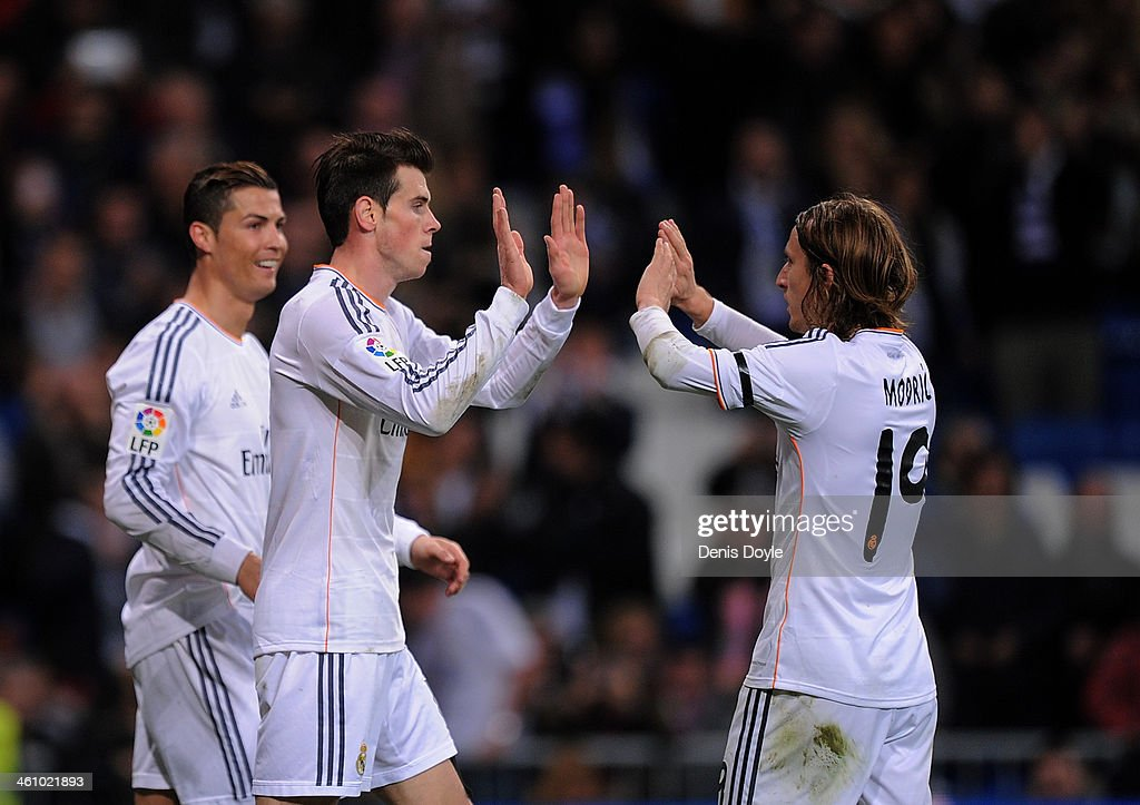 <a gi-track='captionPersonalityLinkClicked' href=/galleries/search?phrase=Gareth+Bale&family=editorial&specificpeople=609290 ng-click='$event.stopPropagation()'>Gareth Bale</a> (C) and <a gi-track='captionPersonalityLinkClicked' href=/galleries/search?phrase=Luka+Modric&family=editorial&specificpeople=560350 ng-click='$event.stopPropagation()'>Luka Modric</a> celebrate after <a gi-track='captionPersonalityLinkClicked' href=/galleries/search?phrase=Cristiano+Ronaldo+-+Soccer+Player&family=editorial&specificpeople=162689 ng-click='$event.stopPropagation()'>Cristiano Ronaldo</a> (L) scored Real's 3rd goal during the La Liga match between Real Madrid CF and RC Celta de Vigo at the Santiago Bernabeu stadium on January 6, 2014 in Madrid, Spain.