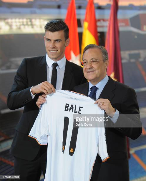 Gareth Bale holds up his new Real Madrid shirt with Real President Florentino Perez during his official unveiling at estadio Santiago Bernabeu on...
