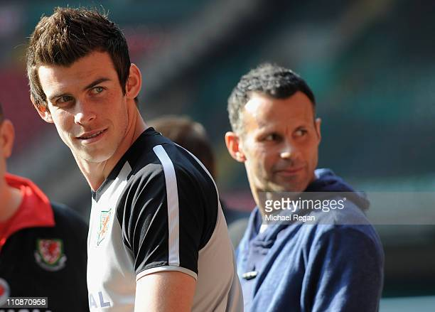 Gareth Bale looks on as he sits out with an injury with Ryan Giggs during the Wales training session ahead of their UEFA EURO 2012 qualifier against...