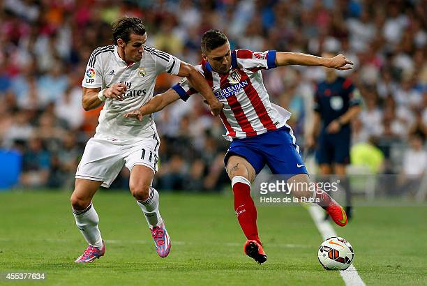 Gareth Bale of Real Madrid and Guilherme Siqueira of Atletico de Madrid compete for the ball during the La Liga match between Real Madrid CF and Club...