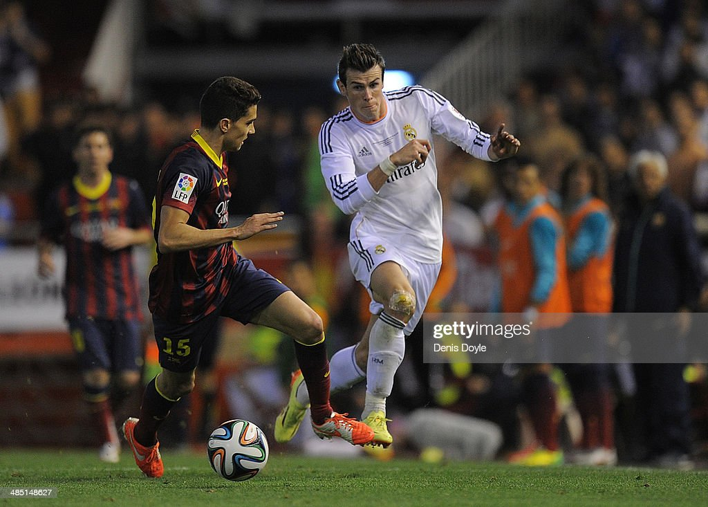 Gareth Bale (R) of Real Madrid beats Marc Bartra of Barcelona during the Copa del Rey Final between Real Madrid and Barcelona at Estadio Mestalla on April 16, 2014 in Valencia, Spain.