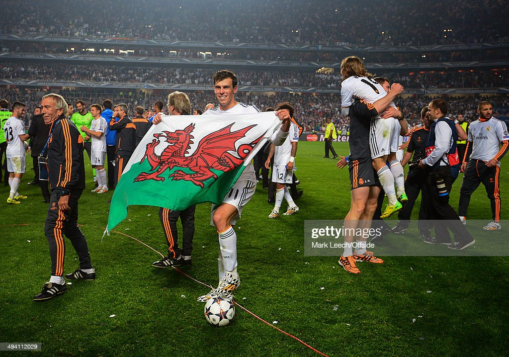 Gareth Bale of Real Madrid celebrates with a Welsh flag during the UEFA Champions League Final between Real Madrid and Atletico de Madrid at Estadio da Luz on May 24, 2014 in Lisbon, Portugal.