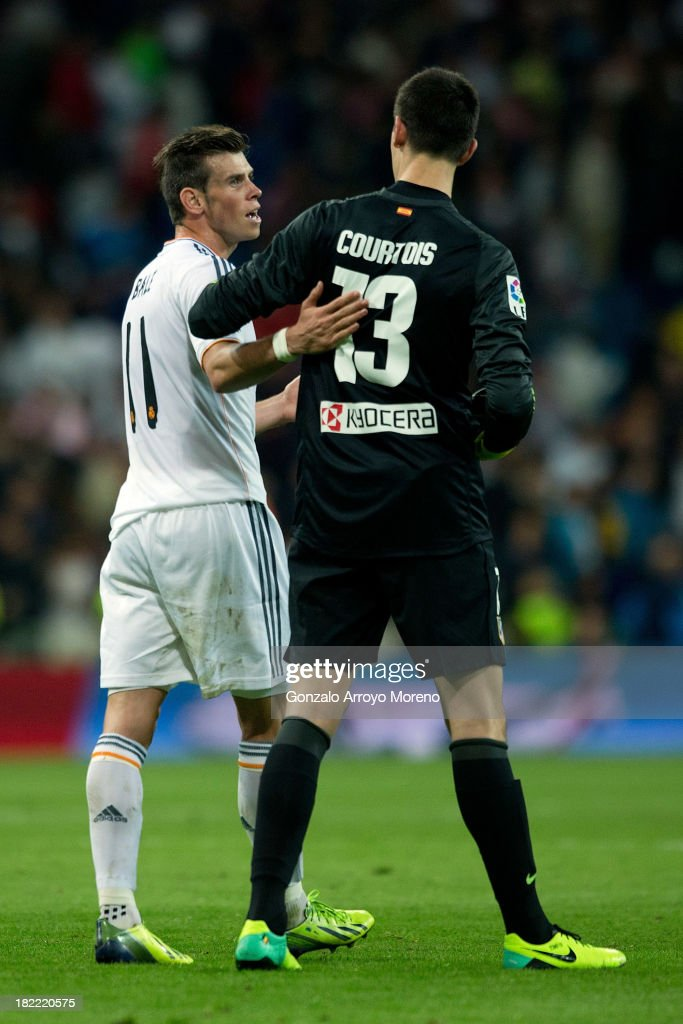 Gareth Bale (L) of Real Madrid CF apologizes to goalkeeper Thibaut Courtois (R) of Atletico de Madrid for his tackle during the La Liga match between Real Madrid CF and Club Atletico de Madrid at Estadio Santiago Bernabeu on September 28, 2013 in Madrid, Spain.