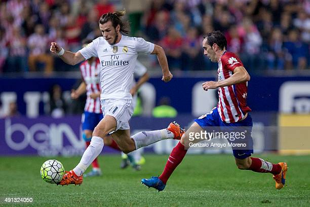Gareth Bale of Real Madrid CF competes for the ball with Diego Godin of Atletico de Madrid during the La Liga match between Club Atletico de Madrid...