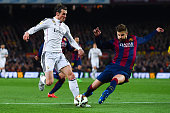 Gareth Bale of Real Madrid CF competes for the ball with Gerard Pique of FC Barcelona during the La Liga match Between FC Barcelona and Real Madrid...