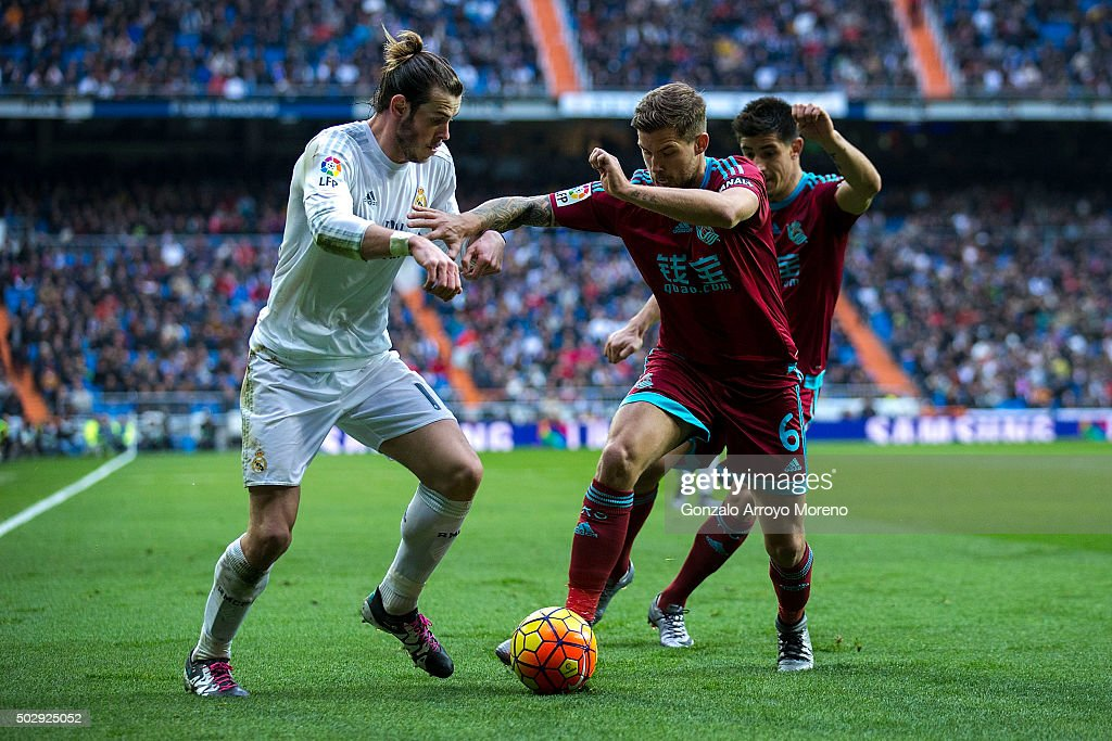 Gareth Bale of Real Madrid CF competes for the ball with Inigo Martinez of Real Sociedad de Futbol during the La Liga match between Real Madrid CF...