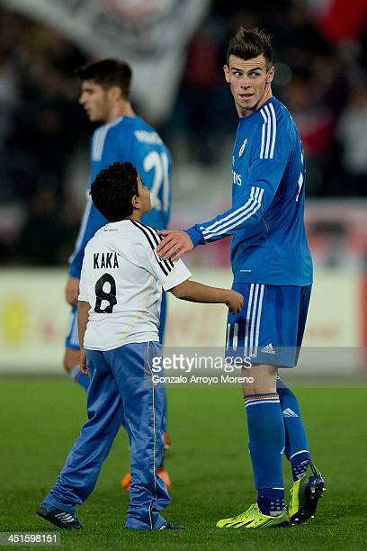 Gareth Bale of Real Madrid CF greets a boy that jumped onto the pitch after the La Liga match between UD Almeria and Real Madrid CF at Estadio de Los...
