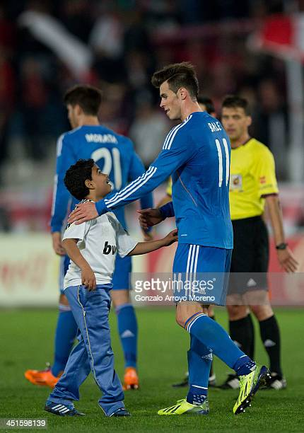 Gareth Bale of Real Madrid CF greets a kid that jumped onto the pitch after the La Liga match between UD Almeria and Real Madrid CF at Estadio de Los...