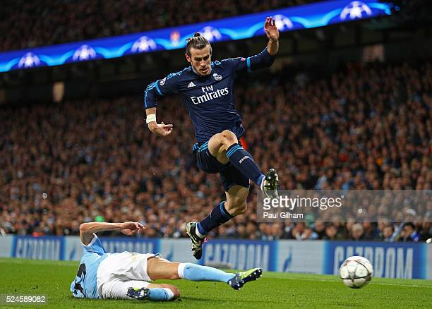 Gareth Bale of Real Madrid CF hurdles the challenge from Jesus Navas of Manchester City during the UEFA Champions League Semi Final first leg match...