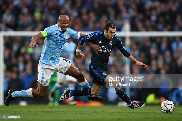 Gareth Bale of Real Madrid CF is challenged by Vincent Kompany of Manchester City during the UEFA Champions League Semi Final first leg match between...