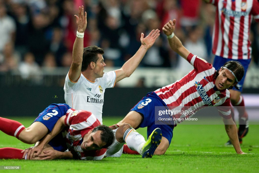 Gareth Bale (2ndL) of Real Madrid CF protests after clashing with Diego Godin (L) and Filipe Luis (R) of Atletico de Madrid during the La Liga match between Real Madrid CF and Club Atletico de Madrid at Estadio Santiago Bernabeu on September 28, 2013 in Madrid, Spain.