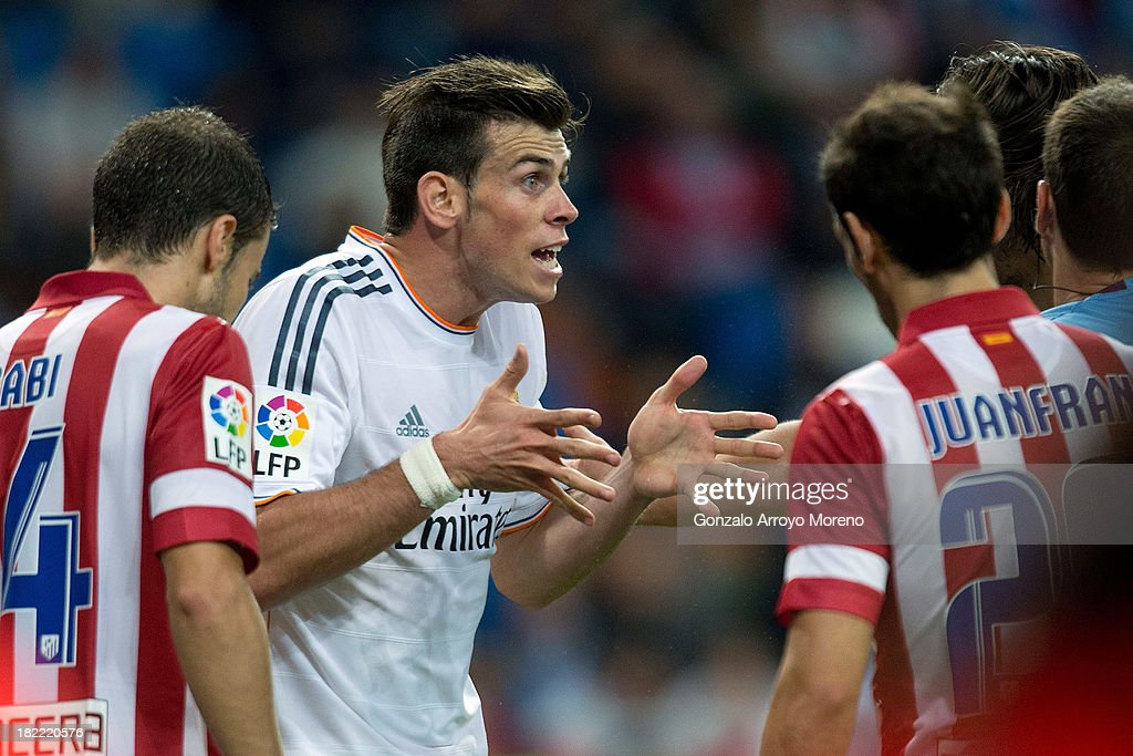 Gareth Bale of Real Madrid CF protests to the referee surrounded by Atletico de Madrid players after failing to score during the La Liga match between Real Madrid CF and Club Atletico de Madrid at Estadio Santiago Bernabeu on September 28, 2013 in Madrid, Spain.