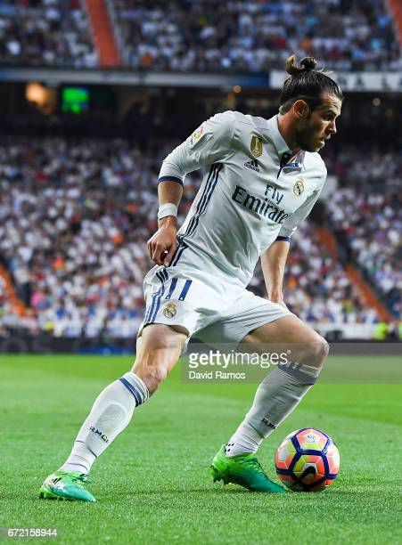 Gareth Bale of Real Madrid CF runs with the ball during the La Liga match between Real Madrid CF and FC Barcelona at the Santiago Bernabeu stadium on...