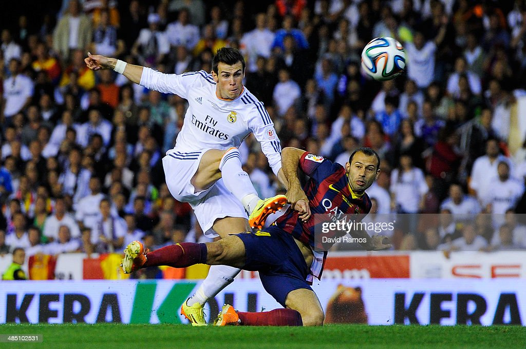 Gareth Bale of Real Madrid CF shoots towards goal under a challenge by Javier Mascherano of FC Barcelona during the Copa del Rey Final between Real Madrid and FC Barcelona at Estadio Mestalla on April 16, 2014 in Valencia, Spain.