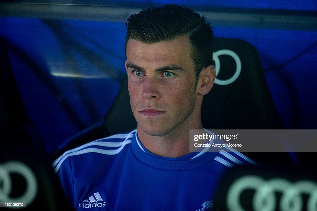 Gareth Bale of Real Madrid CF sits on the bench prior to start the La Liga match between Real Madrid CF and Club Atletico de Madrid at Estadio Santiago Bernabeu on September 28, 2013 in Madrid, Spain.