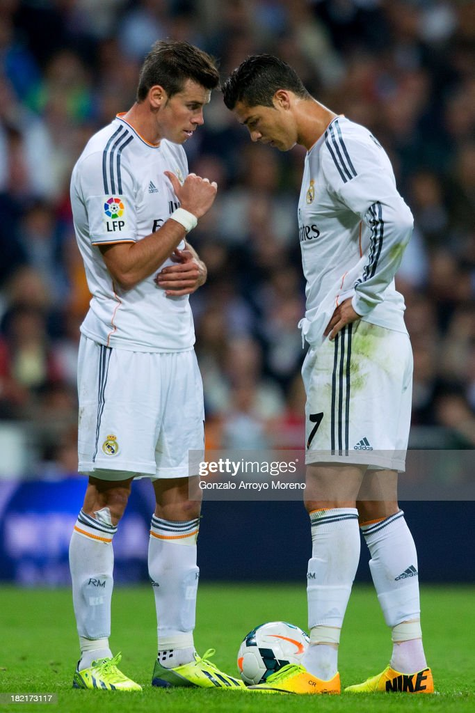 Gareth Bale (L) of Real Madrid CF talks with his teammate Cristiano Ronaldo during the La Liga match between Real Madrid CF and Club Atletico de Madrid at Estadio Santiago Bernabeu on September 28, 2013 in Madrid, Spain.