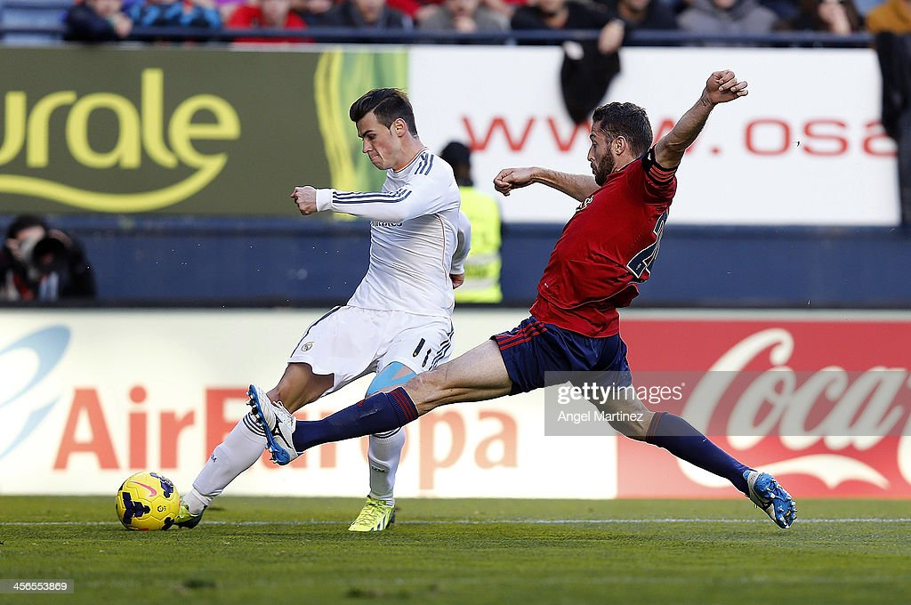 Gareth Bale of Real Madrid competes for the ball with Damia Abella of CA Osasuna during the La Liga match between CA Osasuna and Real Madrid at Estadio Reyno de Navarra on December 14, 2013 in Pamplona, Spain.