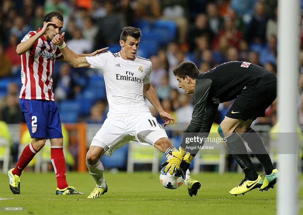 Gareth Bale of Real Madrid competes for the ball with goalkeeper Thibaut Courtois of Atletico de Madrid during the La Liga match between Real Madrid and Club Atletico de Madrid at Estadio Santiago Bernabeu on September 28, 2013 in Madrid, Spain.