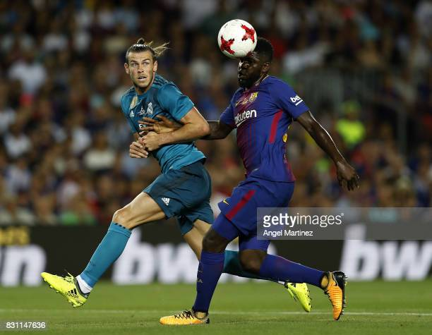 Gareth Bale of Real Madrid competes for the ball with Samuel Umtiti of FC Barcelona during the Supercopa de Espana Final first leg match between FC...