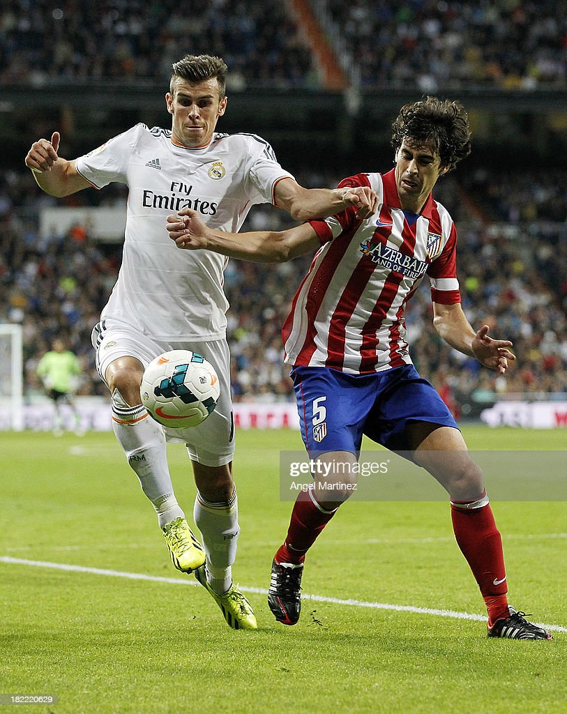 Gareth Bale of Real Madrid competes for the ball with Tiago Cardoso of Atletico de Madrid during the La Liga match between Real Madrid and Club Atletico de Madrid at Estadio Santiago Bernabeu on September 28, 2013 in Madrid, Spain.