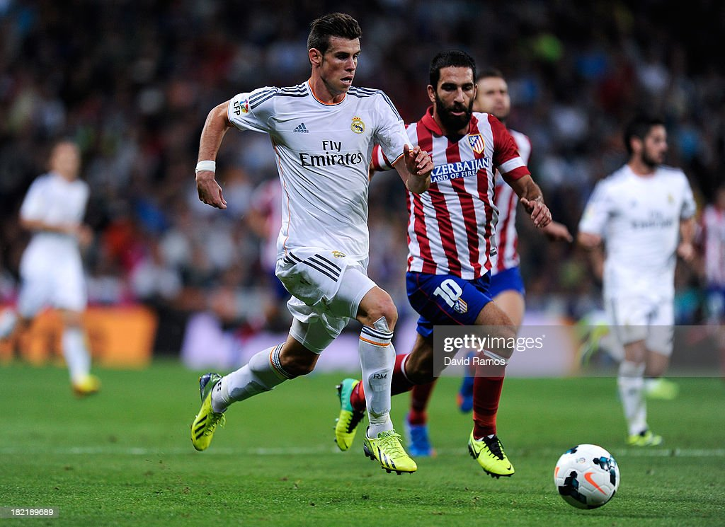 Gareth Bale of Real Madrid duels for the ball with Arda Turan of Atletico de Madrid during the La Liga match between Real Madrid CF and Club Atletico de Madrid at Bernabeu on September 28, 2013 in Madrid, Spain.