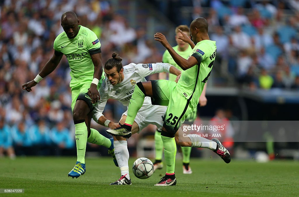 Gareth Bale of Real Madrid gets caught between Eliaquim Mangala and Fernandinho of Manchester City during the UEFA Champions League Semi Final second leg match between Real Madrid and Manchester City FC at Estadio Santiago Bernabeu on May 4, 2016 in Madrid, Spain.