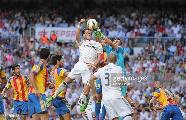 Gareth Bale of Real Madrid goes for a high ball against Diego Alves of Valencia CF during the La Liga match between Real Madrid CF and Valencia CF at...