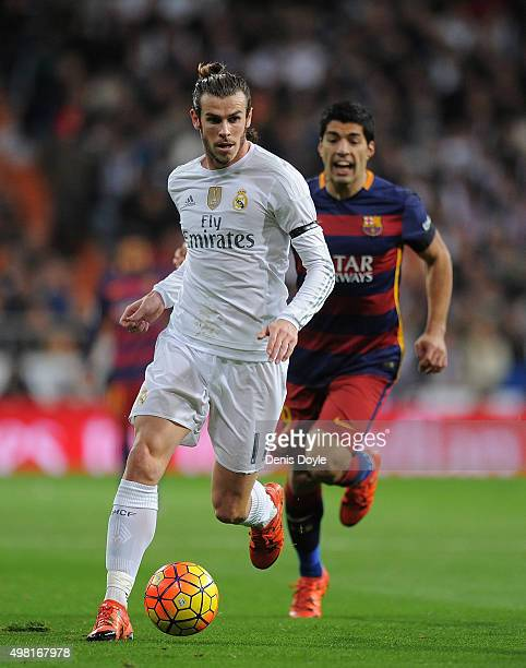 Gareth Bale of Real Madrid is chased by Luis Suarez of FC Barcelona during the La Liga match between Real Madrid and Barcelona at Estadio Santiago...