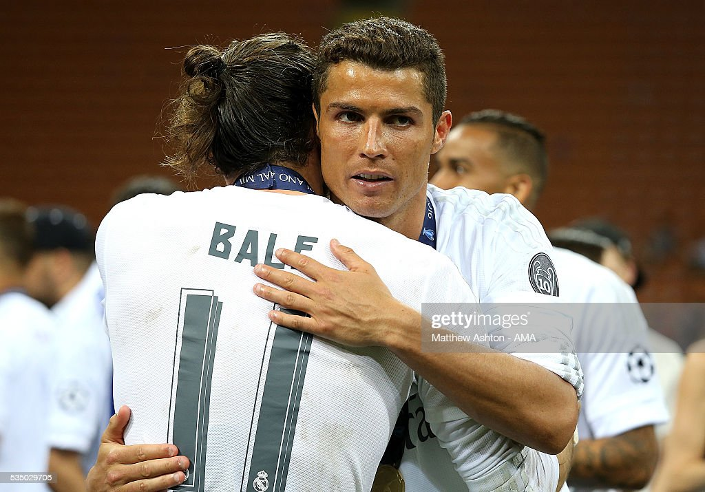 Gareth Bale of Real Madrid is embraced by Cristiano Ronaldo following their team's victory in a penalty shootout during the UEFA Champions League final match between Real Madrid and Club Atletico de Madrid at Stadio Giuseppe Meazza on May 28, 2016 in Milan, Italy.
