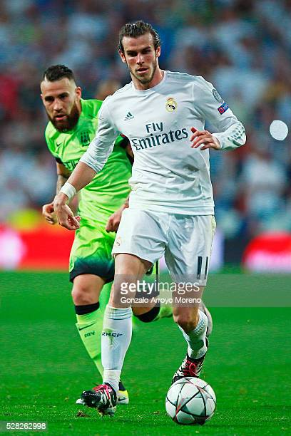 Gareth Bale of Real Madrid is pursued by Nicolas Otamendi of Manchester City during the UEFA Champions League semi final second leg match between...