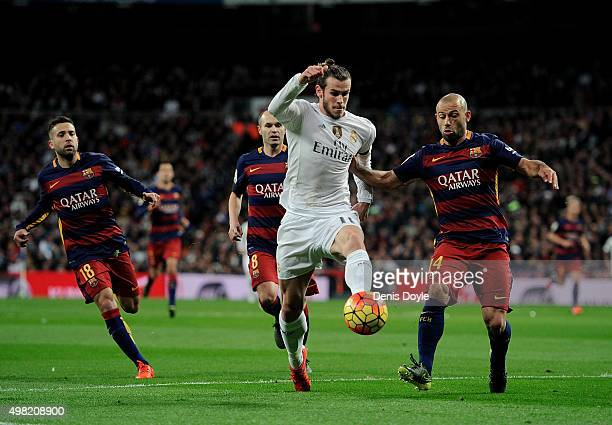 Gareth Bale of Real Madrid is tackled by Javier Mascherano of FC Barcelona during the La Liga match between Real Madrid and Barcelona at Estadio...