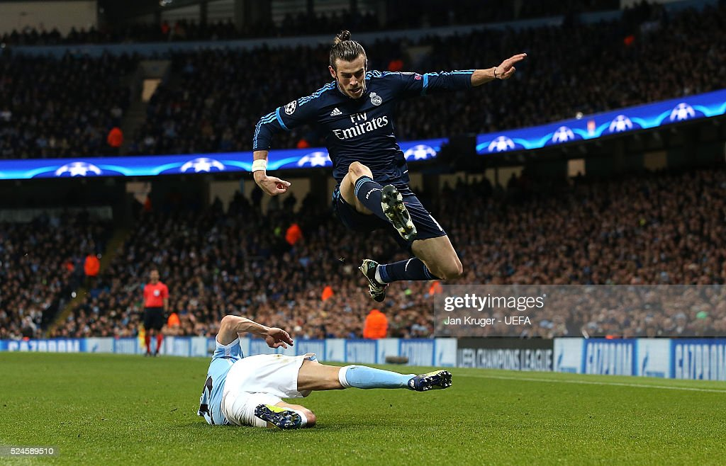 Gareth Bale of Real Madrid leaps over the tackle of Jesus Navas of Manchester City FC during the UEFA Champions League semi final first leg match between Manchester City FC and Real Madrid on April 26, 2016 in Manchester, England.