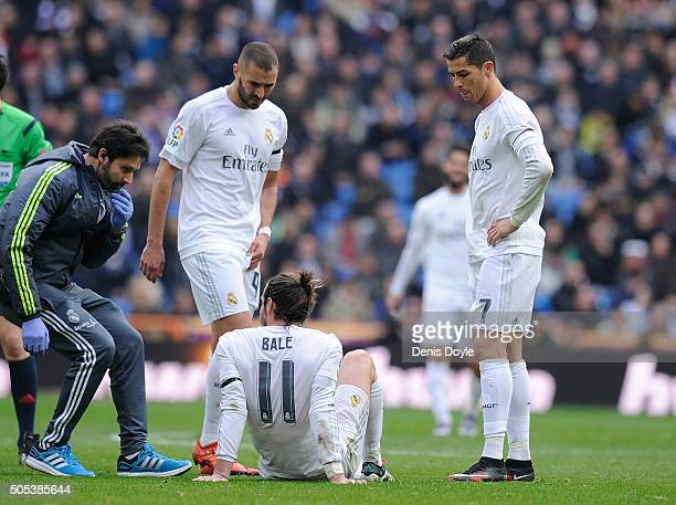 Gareth Bale of Real Madrid lies injured beside Cristiano Ronaldo and Karim Benzema during the La Liga match between Real Madrid CF and Sporting Gijon...