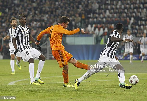 Gareth Bale of Real Madrid scores his team's second goal past Kwadwo Asamoah of Juventus during the UEFA Champions League Group B match between...