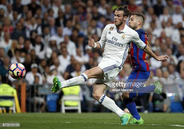Gareth Bale of Real Madrid shoots on goal under pressure from Jordi Alba of FC Barcelona during the La Liga match between Real Madrid and FC...
