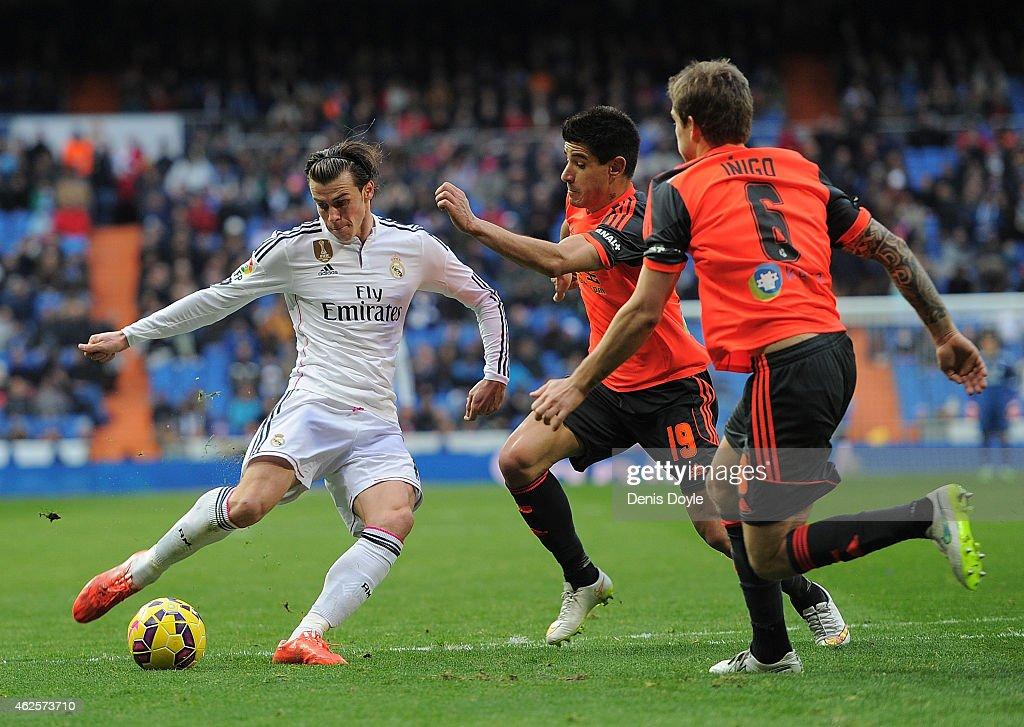 Gareth Bale of Real Madrid shoots past Yuri Berchiche (#19) and Inigo Martinez of Real Sociedad de Futbol complains to the linesman during the La Liga match between Real Madrid CF and Real Sociedad de Futbol at Estadio Santiago Bernabeu on January 31, 2015 in Madrid, Spain.