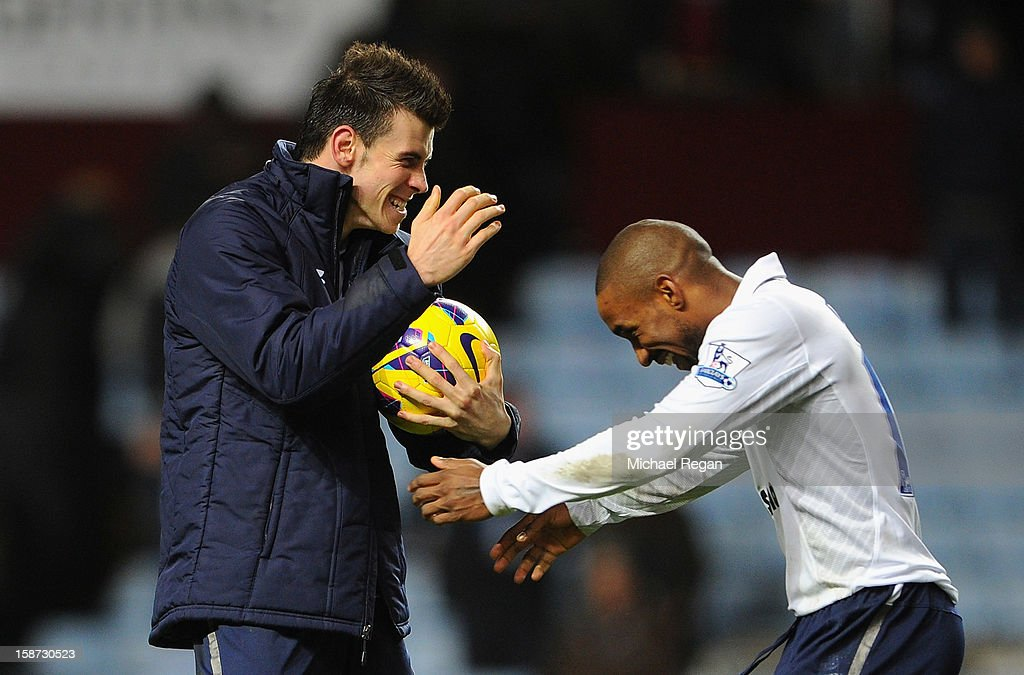 Gareth Bale of Tottenham Hotspur celebrates with the match ball and Jermain Defoe after scoring his hat-trick during the Barclays Premier League match between Aston Villa and Tottenham Hotspur at Villa Park on December 26, 2012 in Birmingham, England.